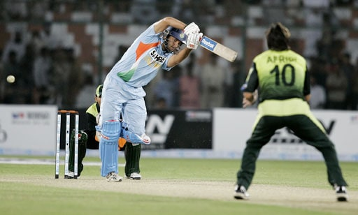 Yuvraj Singh plays a shot as Pakistani all-rounder Shahid Afridi looks on during their Asia Cup match at National Stadium in Karachi, Pakistan on June 26, 2008.