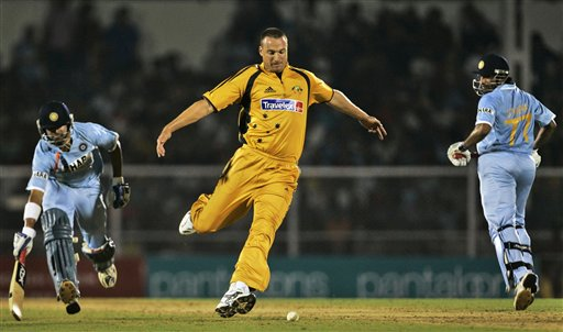 Australian cricketer Stuart Clark, center, attempts to dismiss India's Gautam Gambhir, left, with a run-out, as teammate Robin Uthappa, right, looks on during their Twenty20 match in Mumbai, India, Saturday, Oct. 20, 2007.