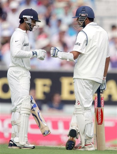 India's Dinesh Karthik, left with Rahul Dravid touch gloves as India pass the 100 run mark as they play England during the first days play at the third cricket test at the Oval in London on Thursday.