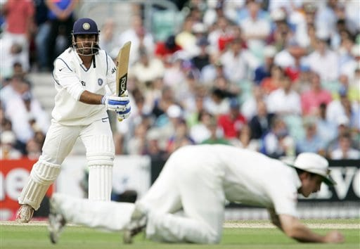 India's Mahendra Singh Dhoni, background, watches as his shot is blocked by England's Andrew Strauss on the fourth days play of the third cricket test at the Oval cricket ground in London on Sunday.