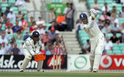 England's Michael Vaughn plays a shot off the bowling of Sacin Tendulkar as keeper Dhoni looks on the fifth days play of the third cricket test at the Oval cricket ground in London, Monday, Aug. 13, 2007.
