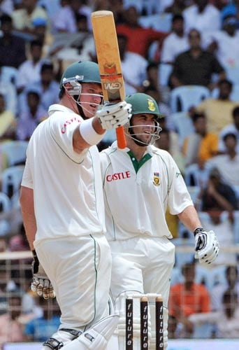 Graeme Smith, left, acknowledges the crowd after scoring 50 runs against India as teammate Niel McKenzie walks in during the first Test of the Future Cup cricket series in Chennai on Wednesday, March 26, 2008.