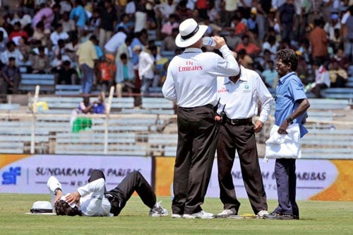 Field umpire Asad Rauf lays on the ground as his counterpart Tony Hill drinks water during the first Test of the Future Cup series in Chennai on Wednesday, March 26, 2008.