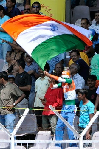 An Indian cricket enthusiast waves a national flag during the first Test of the Future Cup series in Chennai on Wednesday, March 26, 2008.