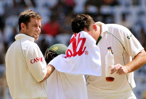 South Africa's captain Graeme Smith, right, wipes his sweat as his opening partner Niel McKenzie holds the towel at a break during the first Test of the Future Cup cricket series in Chennai on Wednesday, March 26, 2008.