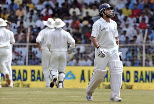 Sachin Tendulkar walks back after his dismissal as South Africa's cricketers, left, run to join the celebration, during the fourth day of the first Test match of the Future Cup series in Chennai on March 29, 2008.
