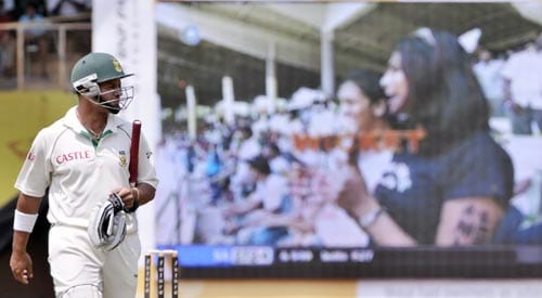 Ashwell Prince, left, walks back after his dismissal as Indian cricket enthusiasts celebrating is seen on a giant screen, right, during the fifth day of the first Test of Future Cup series in Chennai on Sunday, March 30, 2008.