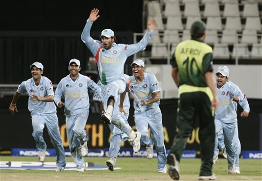 Indian cricket players celebrate their victory as Pakistan's Shahid Afridi, second from right, leaves the ground.