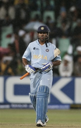 Mahendra Singh Dhoni covers his bat as it rains during the Twenty20 World Championship Cricket match against Pakistan in Durban, South Africa, Friday, Sept. 14, 2007.