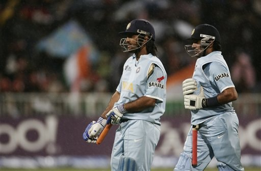 Mahendra Singh Dhoni, left and Robin Uthapa cover their bat as it rains during Twenty20 World Championship Cricket match against Pakistan in Durban, South Africa, Friday, Sept. 14, 2007.