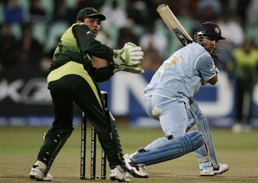 Mahendra Singh Dhoni, right, plays a shot as Pakistan's wicket keeper Kamran Akmal looks on during Twenty20 World Championship Cricket match in Durban, South Africa, Friday, Sept. 14, 2007.