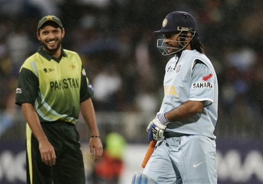 Mahendra Singh Dhoni, right, covers his bat as it rains while Pakistan's Shahid Afridi smiles during Twenty20 World Championship Cricket match in Durban, South Africa, Friday, Sept. 14, 2007.