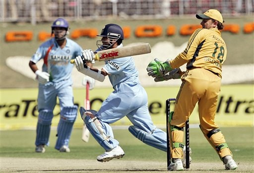 Sachin Tendulkar, center, plays a shot as Australia's Adam Gilchrist, right, looks on during the fourth one day international cricket match in Chandigarh, India, Monday, Oct. 8, 2007.