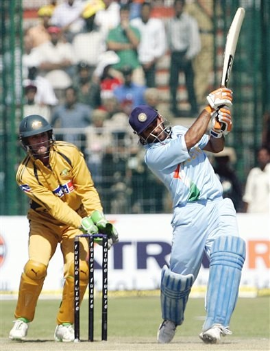 Mahendra Singh Dhoni, right, plays a shot as Australia's Adam Gilchrist, looks on during the fourth one day international cricket match in Chandigarh, India, Monday, Oct. 8, 2007.