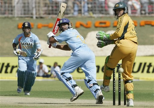 Yuvraj Singh, center, plays a shot as Australia's Adam Gilchrist, right, looks on during the fourth one day international cricket match in Chandigarh, India, Monday, Oct. 8, 2007.