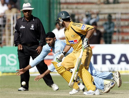 Harbhajan Singh, center, dives to stop the ball as Australia's Ricky Ponting, right looks on, during the fourth one day international cricket match in Chandigarh, India, Monday, Oct. 8, 2007