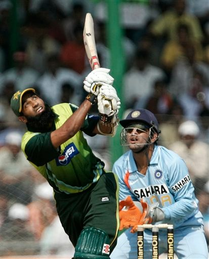Pakistan's Mohammad Yousuf, left, plays a shot as India's Mahendra Dhoni looks on during their first one day international cricket match in Gauhati, India, Monday, Nov. 5, 2007.
