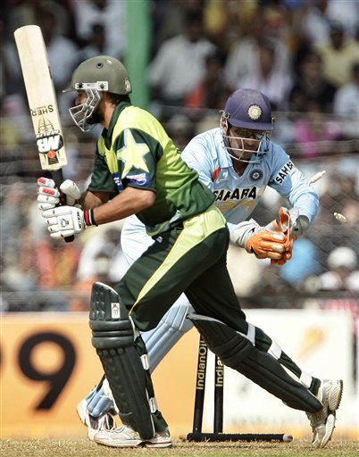 Mahendra Dhoni, right, removes the bails for the dismissal of Pakistan's Shahid Afridi during the first one day international cricket match in Gauhati, India Monday, Nov. 5, 2007.