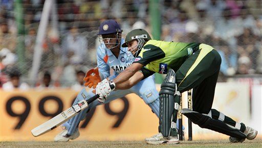 Pakistan's Shahid Afridi, right, attempts to play a shot as India's Mahendra Dhoni looks on, during the first one day international cricket match in Gauhati, India Monday, Nov. 5, 2007.