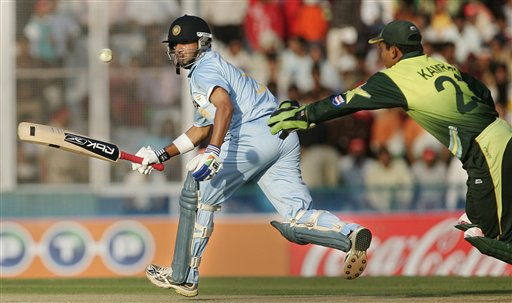 Gautam Gambhir, left, plays a shot as Pakistan's Kamran Akmal tries to field during the second one day international cricket match in Mohali, India, Thursday, Nov. 8, 2007.