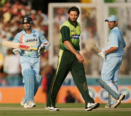 Sachin Tendulkar, left and Gautam Gambhir, right, complete their run as Pakistan's Shahid Afridi looks on during the second one day international cricket match in Mohali, India, Thursday, Nov. 8, 2007