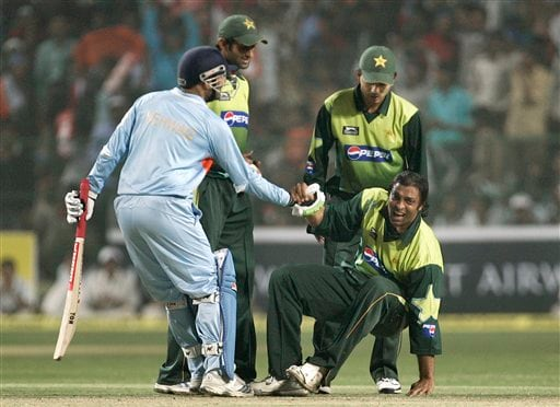 Virender Sehwag, far left, helps Pakistan's Shoaib Akhtar, right, after Akhtar fell on the ground during the fourth one-day international match in Gwalior on Thursday, Nov. 15, 2007.