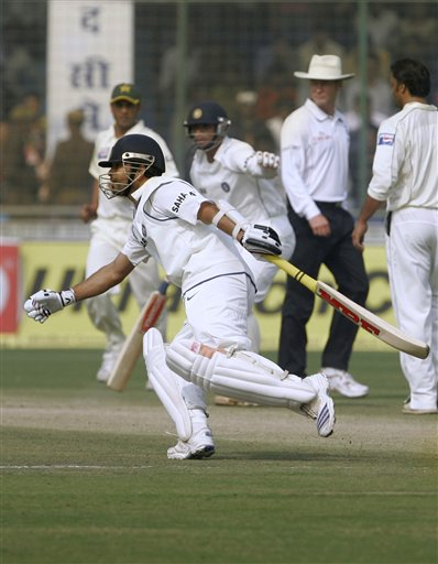 Sachin Tendulkar, foreground, is gestured by Rahul Dravid, background, not to take a run before Tendulkar was run out on the second day of the first Test match, in New Delhi on Friday, Nov 23, 2007.