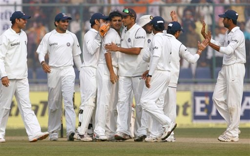 Members of the Indian team celebrate after Sourav Ganguly, forth left, took the wicket of Pakistan's Mohammed Sami, unseen, during the fourth day of the first Test between India and Pakistan in New Delhi on Sunday, Nov 25, 2007.