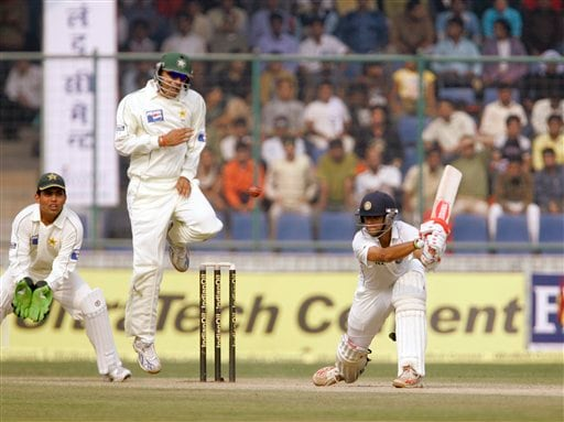 Faizal Iqbal, second left, takes evasive action as he is hit by a shot from Rahul Dravid, right, during the fourth day of the first Test match between India and Pakistan, in New Delhi on Sunday, Nov. 25, 2007.