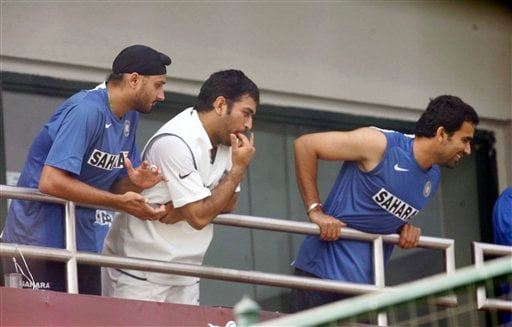 Indian team members, left to right, Harbhajan Singh, Mahinder Singh Dhoni, and Zaheer Khan cheer as teammates Sachin Tendulkar and VVS Laxman, unseen, return to the pavilion after India won the first Test match in New Delhi on Monday, Nov 26, 2007.