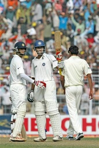 Wasim Jaffer, center, acknowledges the crowd after scoring fifty runs as Rahul Dravid, left, looks on during the first day of the second Test match between India and Pakistan in Kolkata.