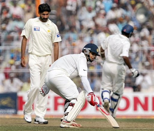 Rahul Dravid, foreground, and Wasim Jaffer, right, run between the wickets as Pakistan bowler Sohail Tanvir walks on during the first day of the second Test match between India and Pakistan in Kolkata.