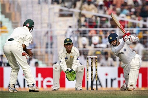 Rahul Dravid takes a shot as Kamran Akmal, center, and Misbah-ul-Haq react during the first day of the second Test match between India and Pakistan in Kolkata.
