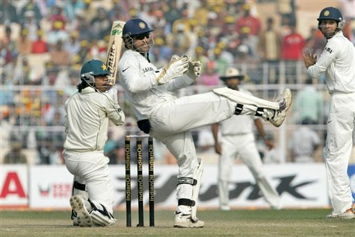 Pakistan's Mohammad Sami, left, plays a shot as Indian wicket keeper Mahendra Dhoni and VVS Laxman react during the fourth day of second Test at Kolkata on Monday, Dec 3, 2007. India leads 1-0 in the three Test series.