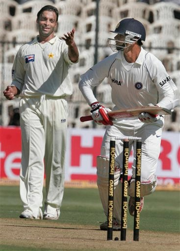 Pakistan's Shoaib Akhtar, left, gestures to India's Rahul Dravid, right, as the latter made an unsuccessful attempt to take a run on the first day of their third and final Test in Bangalore on Saturday, Dec 8, 2007. India leads the series 1-0.