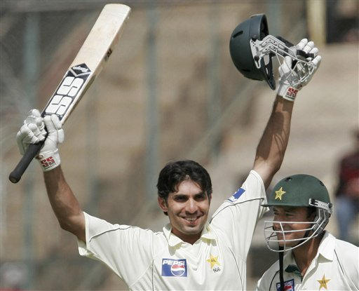 Pakistan's Misbah-ul-Haq, left, raises his bat to celebrate a century as teammate Yasir Arafat looks on during the fourth day of the final Test match against India in Bangalore on Tuesday, Dec 11, 2007. India leads the series 1-0.
