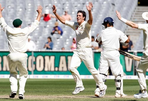 Mitchell Johnson, center, celebrates taking the final wicket of RP Singh, right, during the fourth day of their first Test match at the Melbourne Cricket Ground on Saturday, December 29, 2007. Australia won the match by 337 runs.