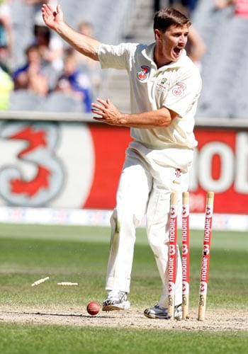 Brad Hogg celebrates after Michael Hussey runs out Harbhajan Singh for no score during the fourth day of their first Test match at the Melbourne Cricket Ground on Saturday, December 29, 2007.