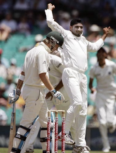 Michael Clarke, left, lowers his head as Harbhajan Singh celebrates taking Clark's wicket. LBW, for 1 run at the Sydney Cricket Ground on Wednesday, January 2, 2008, on the first day of their second cricket Test.