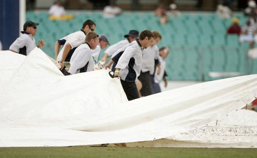 Grounds crew pull a tarpaulin over the wicket during a rain delay at the Sydney Cricket Ground on Saturday, January 5, 2008, on the fourth day of the second cricket Test between Sydney and India. India made 532 in reply to Australia's 463 in their first innings.