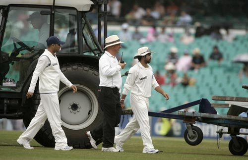 Sachin Tendulkar, right, and Virender Sehwag, left, walk off with umpire Mark Benson during a rain delay at the Sydney Cricket Ground on Saturday, January 5, 2008, on the fourth day of their second cricket Test. India made 532 in reply to Australia's 463 in their first innings.