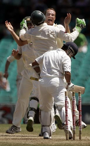 Stuart Clark, top right, celebrates with team-mates after he bowled Sachin Tendulkar, bottom, at the Sydney Cricket Ground on Sunday, January 6, 2008, on the last day of their second cricket Test. Australia has set India a total of 333 for victory in their second innings.