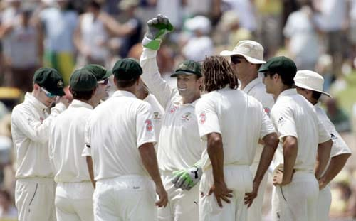 Australia's wicketkeeper Adam Gilchrist, centre, holds a glove up after equalling the world record for Test catches after catching out Harbhajan Singh at the Adelaide Oval on Friday, January 25, 2008, on the second day of their fourth Test.