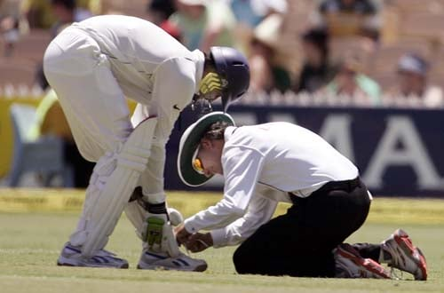 Umpire Billy Bowden, right, ties the shoe lace of Harbhajan Singh as they play against Australia at the Adelaide Oval on Friday, January 25, 2008, on the second day of their fourth Test.