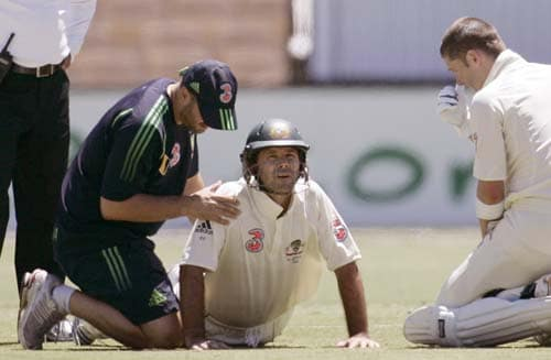 Ricky Ponting, center, is treated by team trainer Alex Kountouris, left, as batting partner Michael Clarke, right, checks on his skipper's condition at the Adelaide Oval on Sunday, January 27, 2008, on the fourth day of their fourth Test against India. India made a first innings total of 526.