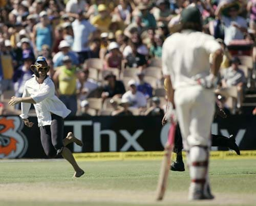 Andrew Symonds, right, watches a pitch invader wearing a monkey mask being chased by security at the Adelaide Oval on Sunday, January 27, 2008, on the fourth day of their fourth Test against India. India made a first innings total of 526.