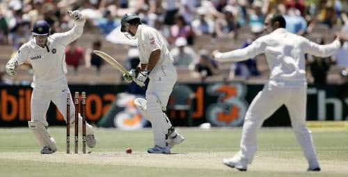 Virender Sehwag, right, bowls Australia's captain Ricky Ponting, center, as wicketkeeper Mahendra Dhoni, left, reacts at the Adelaide Oval on Sunday, January 27, 2008, on the fourth day of their fourth Test. India made a first innings total of 526.