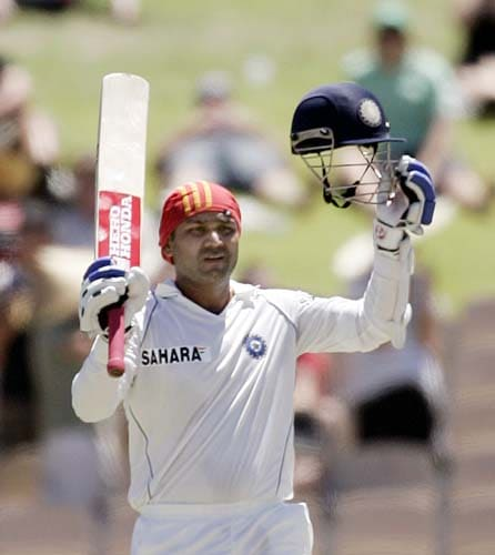 Virender Sehwag raises his bat and helmet after making 100 runs against Australia at the Adelaide Oval on Monday, January 28, 2008, on the last day of their fourth Test. Australia made 563 in reply to India's first innings total of 526.