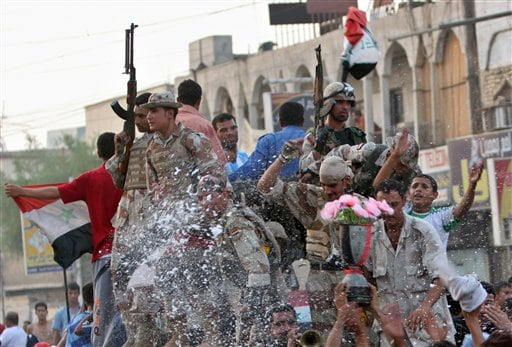 Iraqi soldiers and civilians celebrate in the streets of Basra, 550 kilometers (340 miles) southeast of Baghdad, Iraq after Iraq beat Saudi Arabia in the Asian Cup finals, Sunday, July 29, 2007. Iraq won the final after defeating Saudi Arabia 1-0 in Jakarta.
