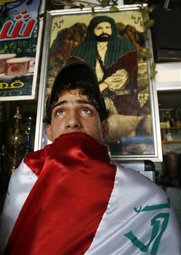 A soccer fan wrapped in the Iraqi flag watches the Iraqi national soccer team play Saudi Arabia in the Asian Cup finals at a shop in the Shiite enclave of Sadr City in Baghdad, Iraq, Sunday, July 29, 2007. Iraq won the final after defeating Saudi Arabia 1-0 in Jakarta.